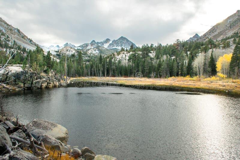 Un lac alpin reflète les crêtes couvertes par neige un jour d'automne en Californie photo stock
