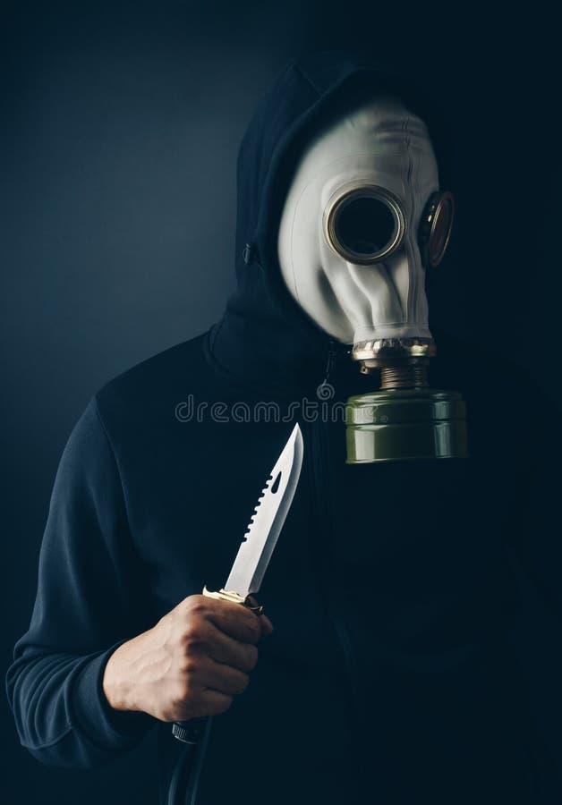 Un ladrón asustadizo en careta antigás con un cuchillo del combate imagen de archivo