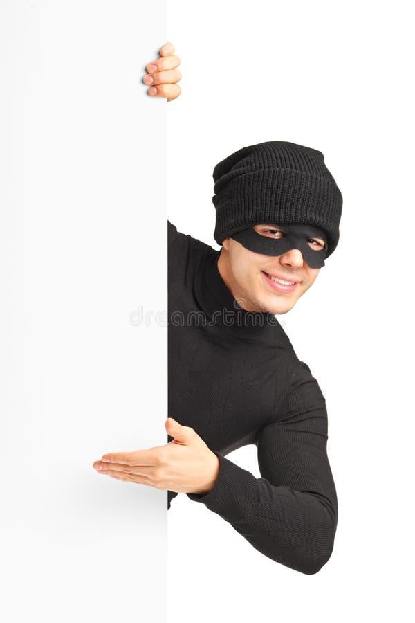Un ladrón con la máscara del robo que gesticula en un panel imagen de archivo