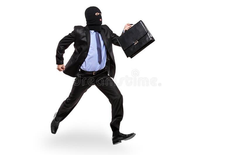 Un ladrón con la máscara del robo que se ejecuta lejos imágenes de archivo libres de regalías