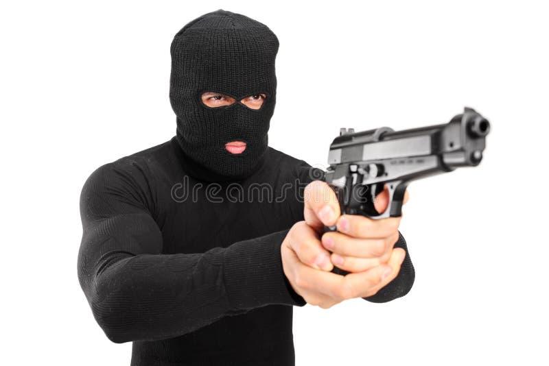 Un ladrón con la máscara del robo que sostiene un arma imagenes de archivo
