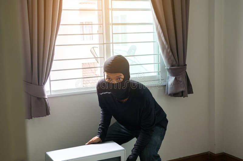 Un ladrón del hombre en máscara negra que roba la TV de la casa fotos de archivo libres de regalías