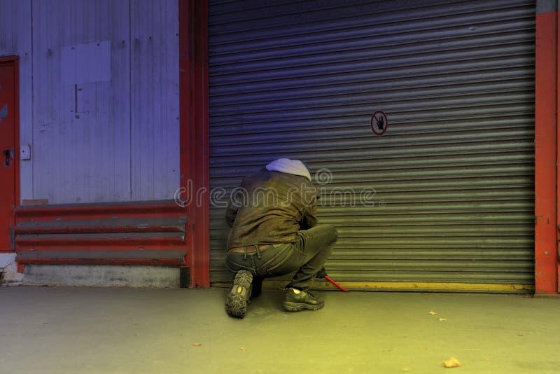 Un ladrón intenta romper una puerta en una compañía con una palanca imagenes de archivo