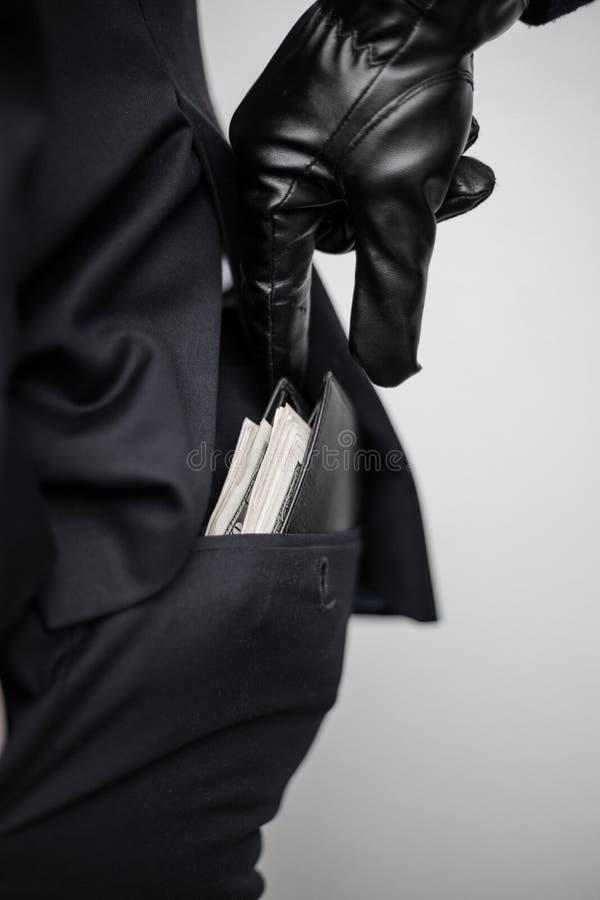 Un ladrón toma una cartera con un efectivo de un bolsillo de un hombre en un s imagen de archivo libre de regalías