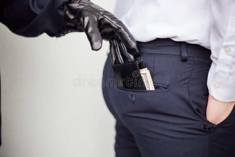 Un ladrón toma una cartera con un efectivo de un bolsillo de un hombre en un s fotos de archivo