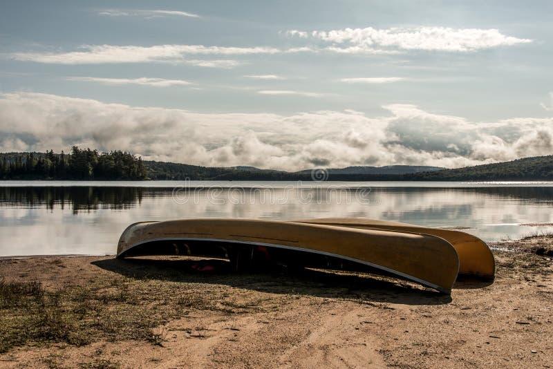 Un lago canada Ontario di due canoe della canoa dei fiumi ha parcheggiato sulla spiaggia vicino all'acqua nel parco nazionale del immagine stock libera da diritti