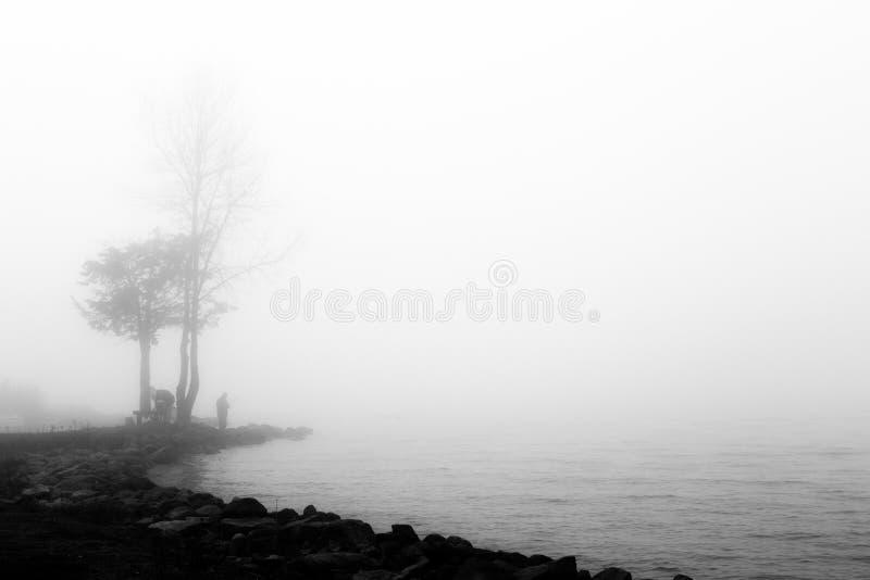 Un lago ocultado por la niebla, con las rocas en el primero plano y un fisherm imágenes de archivo libres de regalías