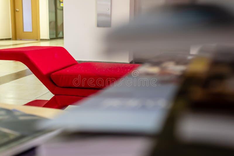 Un lanzamiento de un sofá rojo - foco de la perspectiva del primer en el borde del sofá foto de archivo
