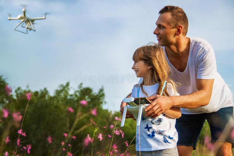 Un lanzamiento del hombre y de la niña un avión radio-controlado o un abejón o un helicóptero en el cielo imagen de archivo