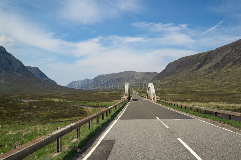 Un largo camino a un puente con la opinión hermosa de la montaña y de las colinas en paisaje asombroso de la montaña fotografía de archivo libre de regalías
