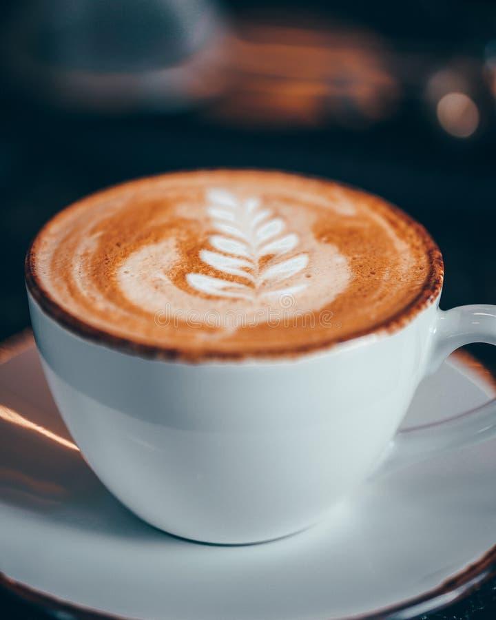 Un latte avec une conception d'art de feuille photographie stock libre de droits