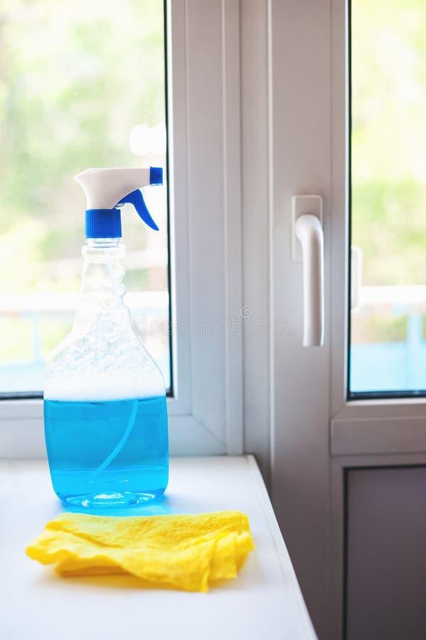 Un laveur de vitres bleu, un chiffon jaune sur un filon-couche blanc de fenêtre contre la fenêtre Mise en oeuvre des inspections  image libre de droits