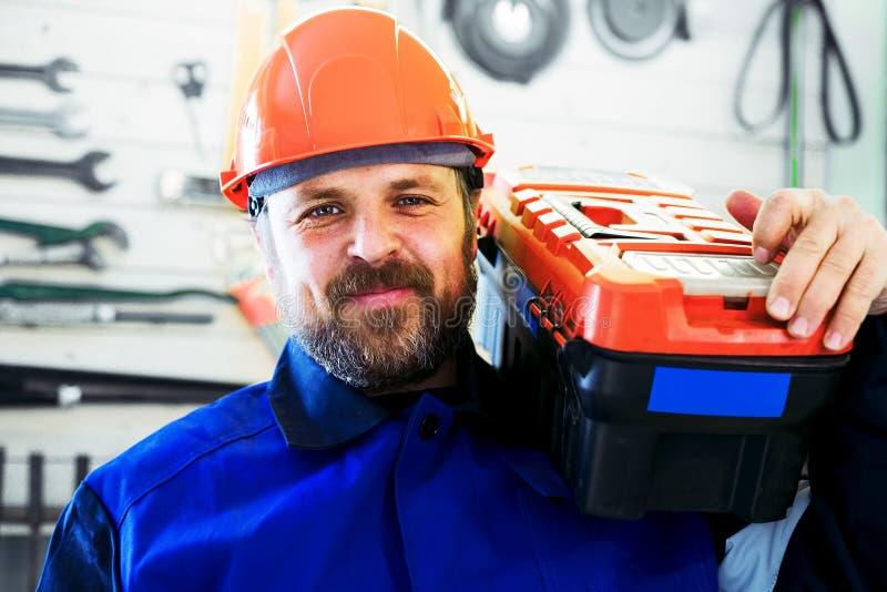 Un lavoratore in un casco con una scatola di strumenti sulla sua spalla esamina direttamente la macchina fotografica ed i sorrisi immagine stock