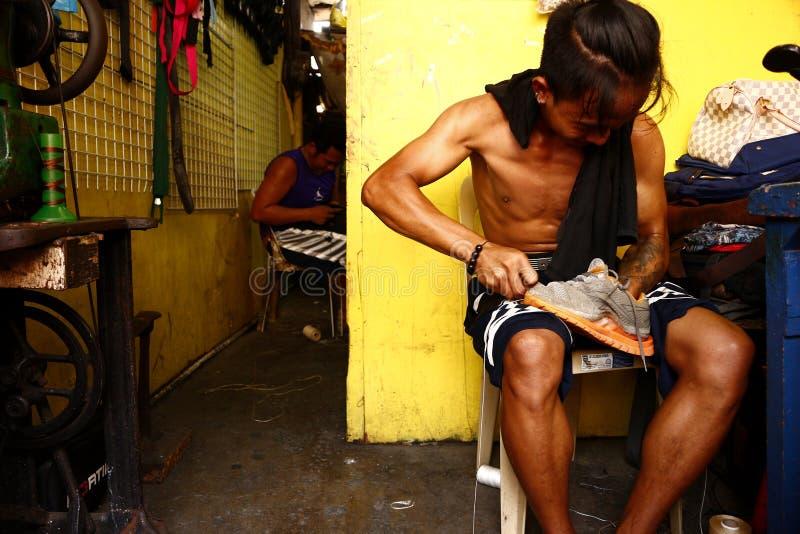 Un lavoratore dell'officina riparazioni della scarpa ripara una vecchia scarpa di gomma per un cliente fotografia stock