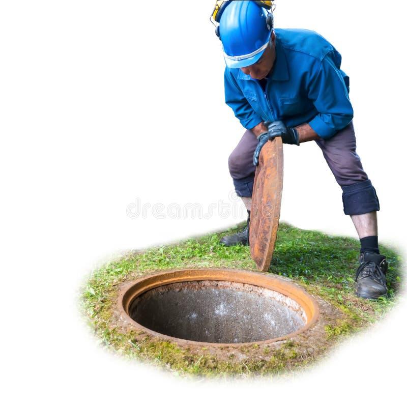 Un lavoratore in un indumento speciale per i lavori di costruzione apre una botola dentro per discendere nel sottosuolo immagini stock libere da diritti