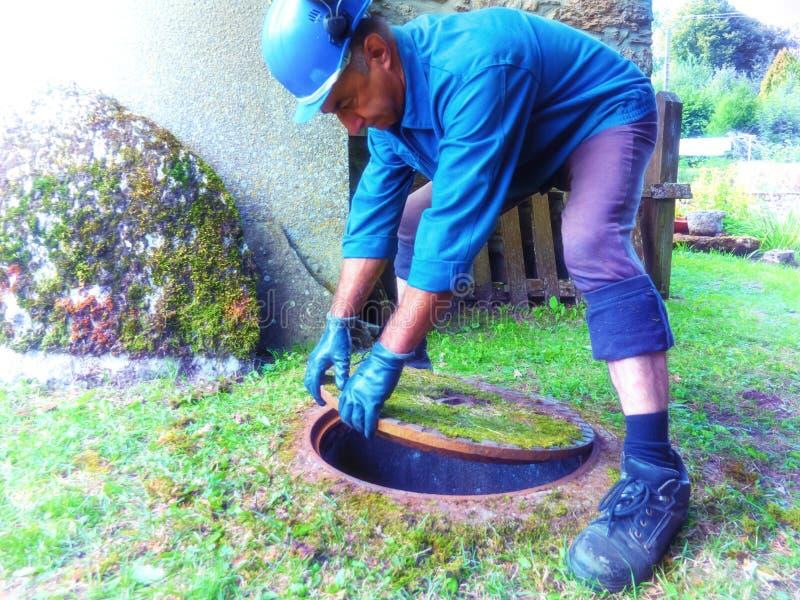 Un lavoratore in un indumento speciale per i lavori di costruzione apre una botola dentro per discendere nel sottosuolo fotografia stock