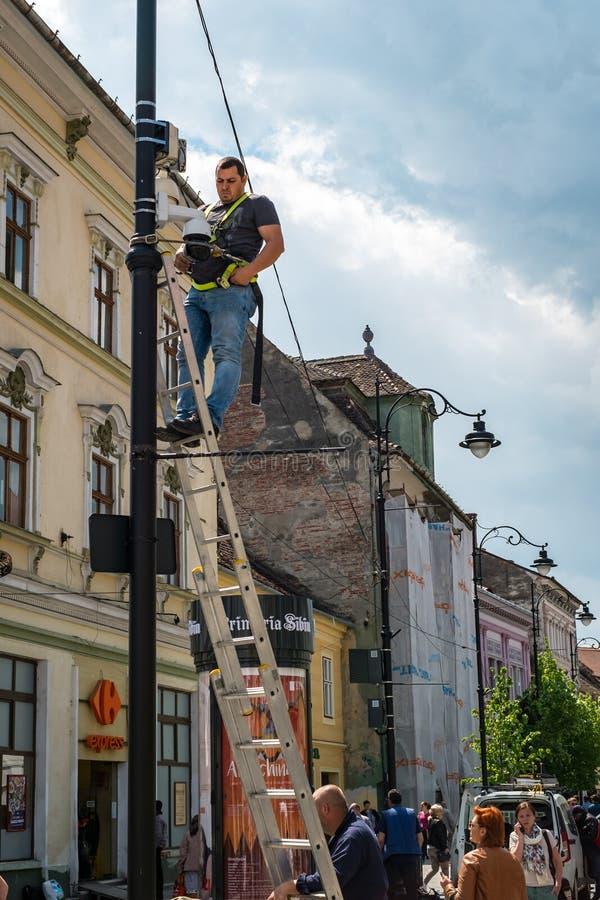Un lavoratore installa una sorveglianza della macchina fotografica fotografia stock
