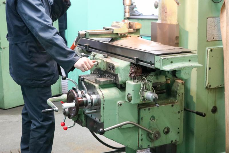 Un lavoratore maschio lavora ad un più grande tornio del fabbro del ferro del metallo, l'attrezzatura per le riparazioni, lavoro  immagini stock libere da diritti