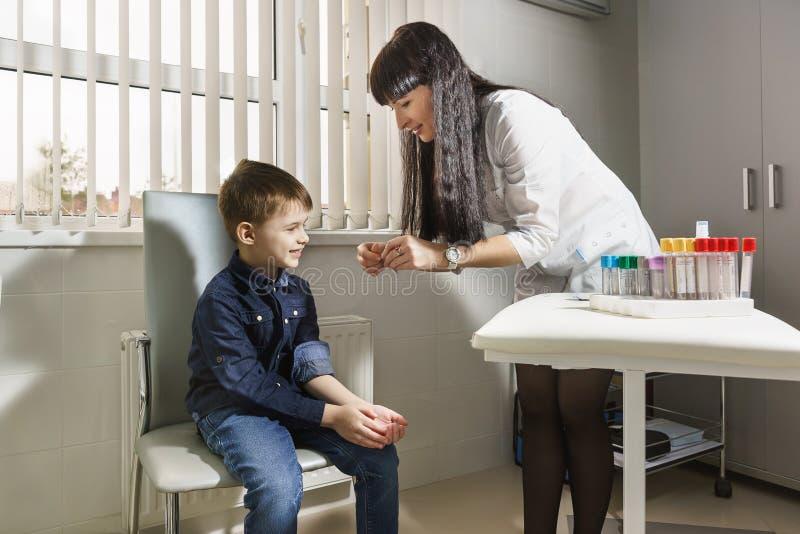 Un lavoratore medico apre un cerotto battericida per un ragazzo sorridente immagini stock libere da diritti