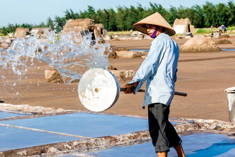 Un lavoratore non identificato del sale che spruzza la pulizia dell'acqua sistema in dist di Hai Hau, Namdinh, Vietnam fotografie stock