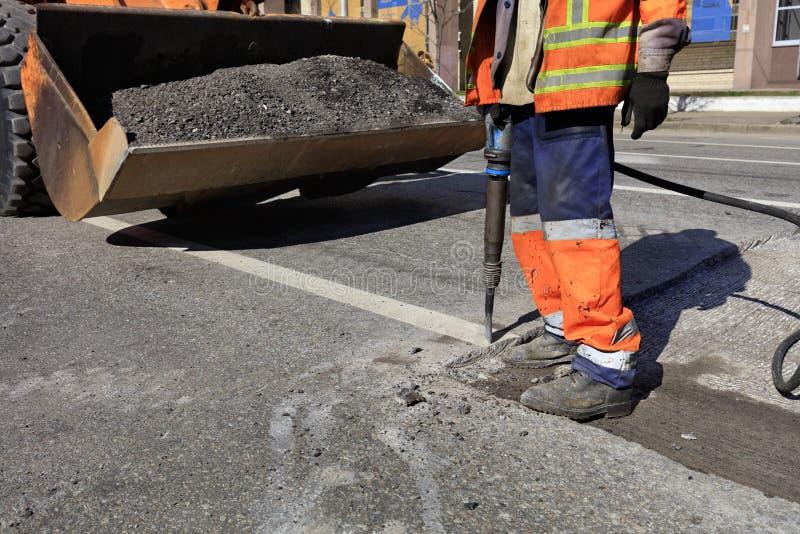 Un lavoratore rimuove un pezzo di asfalto con un martello pneumatico pneumatico nella costruzione di strade immagine stock