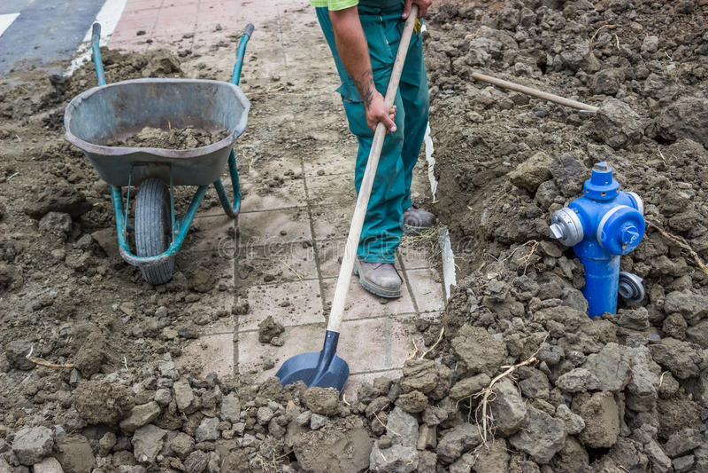 Un lavoratore spala la sporcizia in una carriola 2 immagini stock