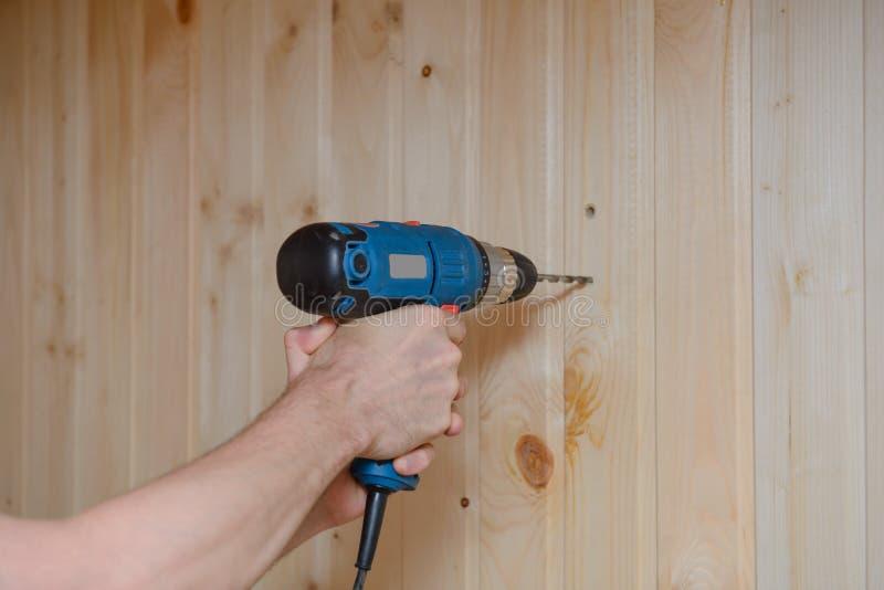 Un lavoratore tiene un trapano e perfora la parete immagini stock