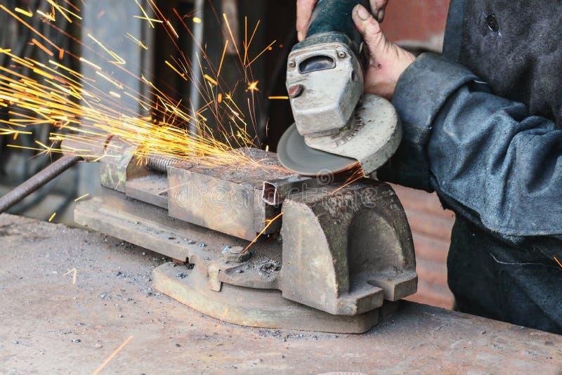 Un lavoratore tratta un tubo del metallo con una piccola smerigliatrice immagine stock