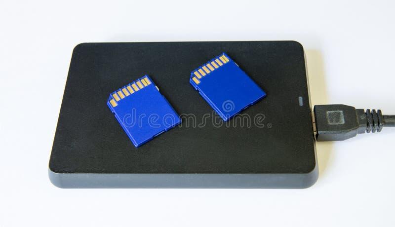 Un lecteur de disque dur externe d'isolement sur un fond blanc avec deux cartes de mémoire de caméra photographie stock libre de droits