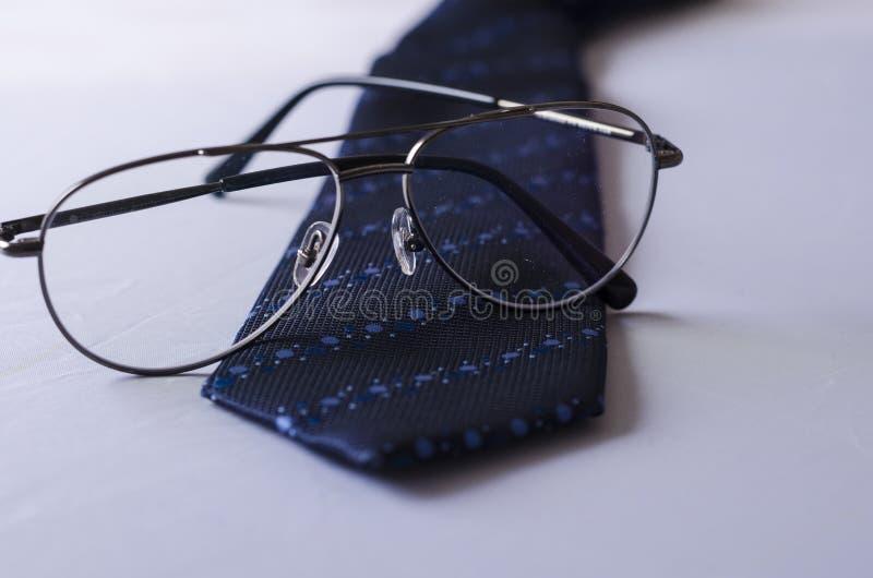 Un legame blu punteggiato con gli occhiali fotografie stock