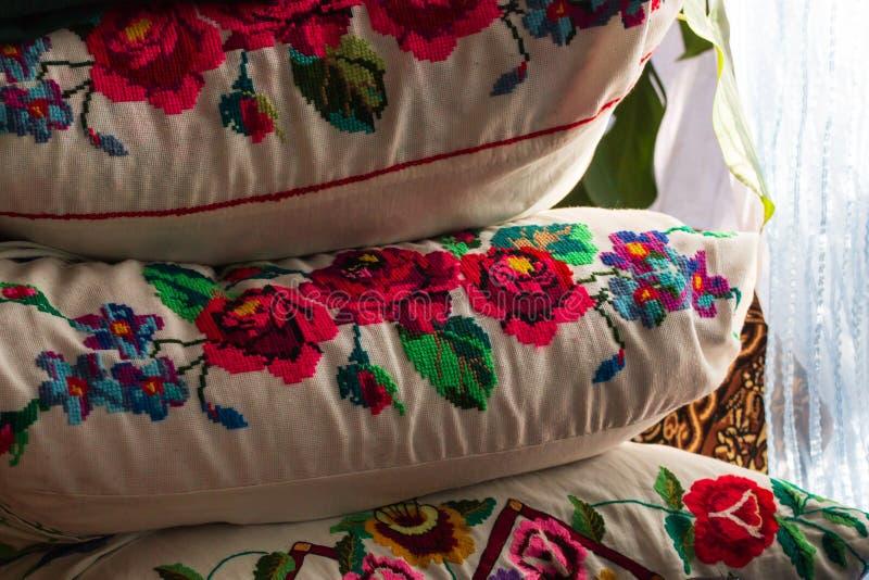 Un letto antico del ferro con i cuscini ricamati Vecchio letto del ferro con i cuscini Cuscini ricamati su un vecchio letto fotografia stock