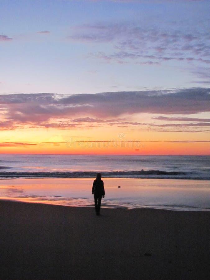 Un lever de soleil de attente de fille sur la plage photo stock
