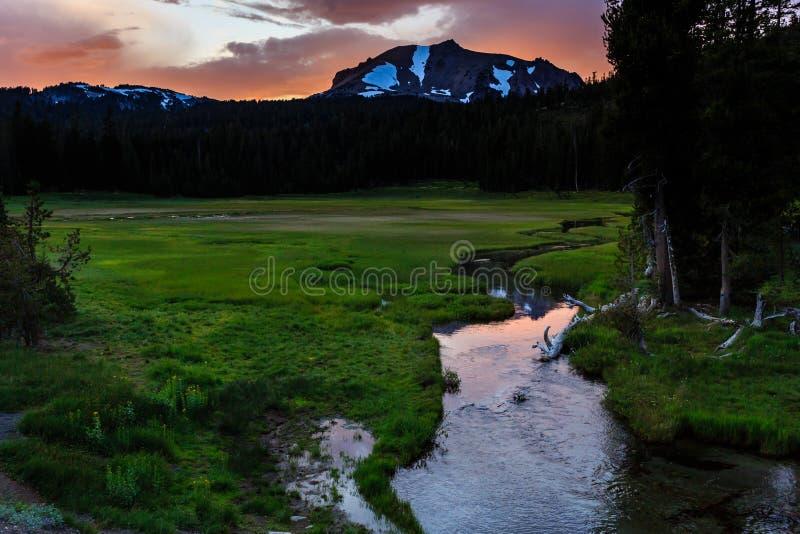 Un lever de soleil rose dramatique au-dessus d'une neige a couvert le dessus de montagne d'un pré vert luxuriant avec un petit co photographie stock