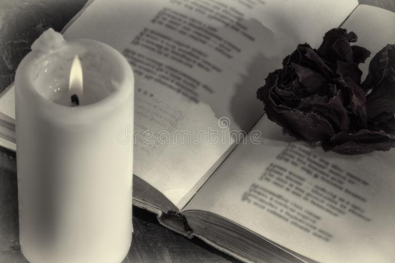 Un libro abierto con una vela en las páginas es un brote de la rosa secada imagenes de archivo