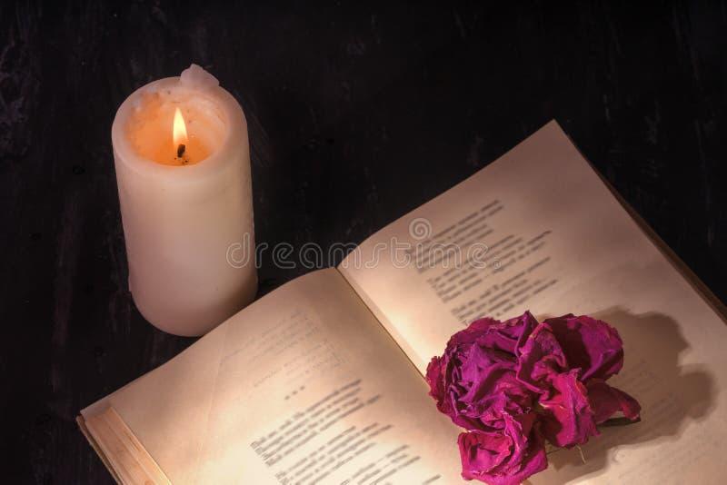 Un libro abierto con una vela en las páginas es un brote de la rosa secada fotos de archivo