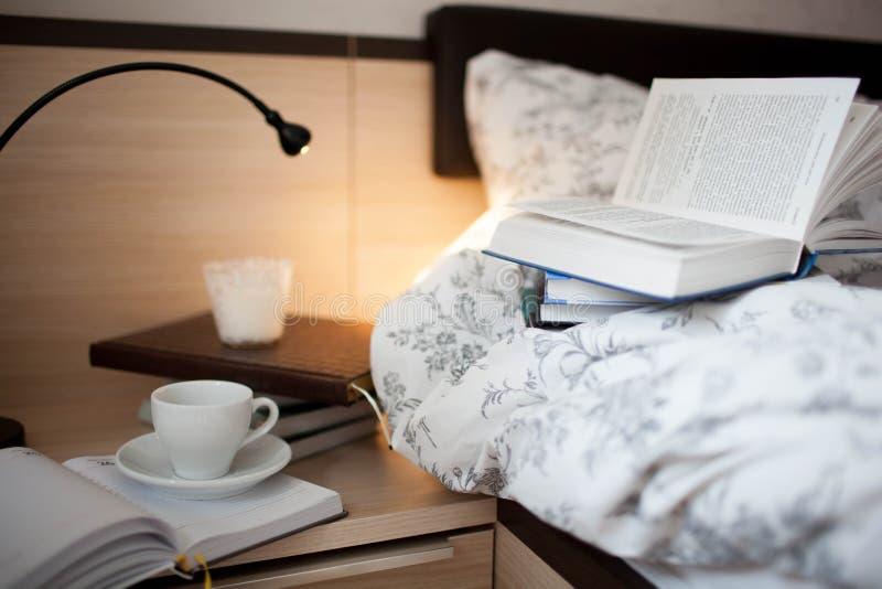 Un libro abierto en la cama Libros y taza de café en el nightstand fotos de archivo libres de regalías