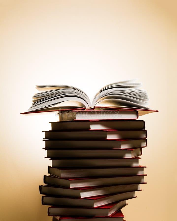Un libro abierto en una pila de libros rojos bajo la forma de espiral foto de archivo libre de regalías