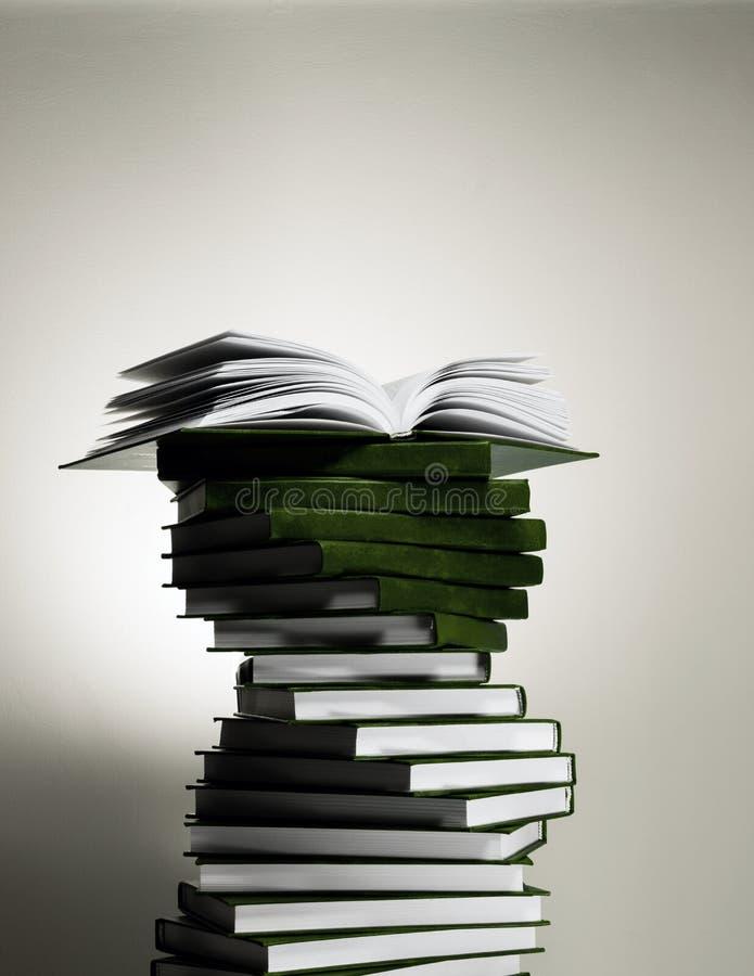 Un libro abierto en una pila de libros rojos bajo la forma de espiral imagenes de archivo