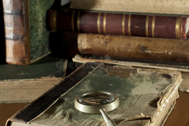 Un libro antico in una copertura stracciata ed in una lente d'ingrandimento su un fondo vago di altri vecchi libri immagine stock libera da diritti