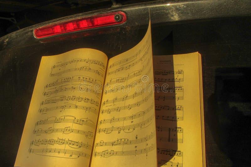 Un libro aperto di vecchi spartiti di musica accanto ad un segnale rosso su un fondo nero fotografia stock