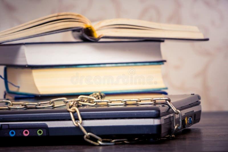 Un libro aperto sta trovandosi su un computer portatile che ? collegato da una catena Libri invece dei computer Amore a read_ immagini stock