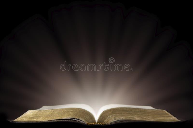 Un libro che assomiglia ad una bibbia aperta in una stanza scura fotografie stock libere da diritti