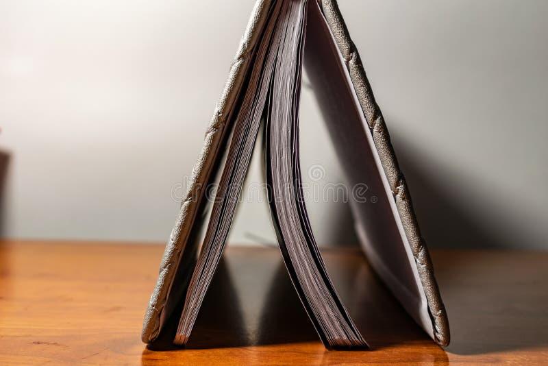 Un libro, un cuaderno con un modelo a cuadros en una tabla de madera en diversas actitudes La cubierta es gris y suave con textur foto de archivo libre de regalías