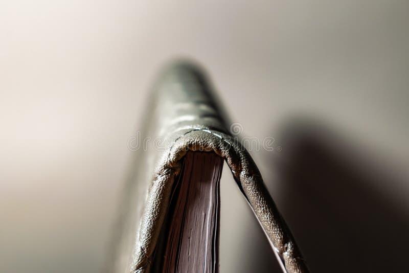 Un libro, un cuaderno con un modelo a cuadros en una tabla de madera en diversas actitudes La cubierta es gris y suave con textur foto de archivo