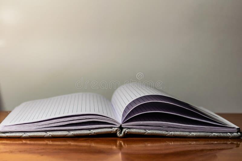 Un libro, un cuaderno con un modelo a cuadros en una tabla de madera en diversas actitudes La cubierta es gris y suave con textur fotos de archivo