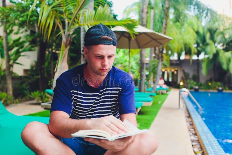Un libro de lectura del hombre al lado de la piscina en el jardín fotos de archivo