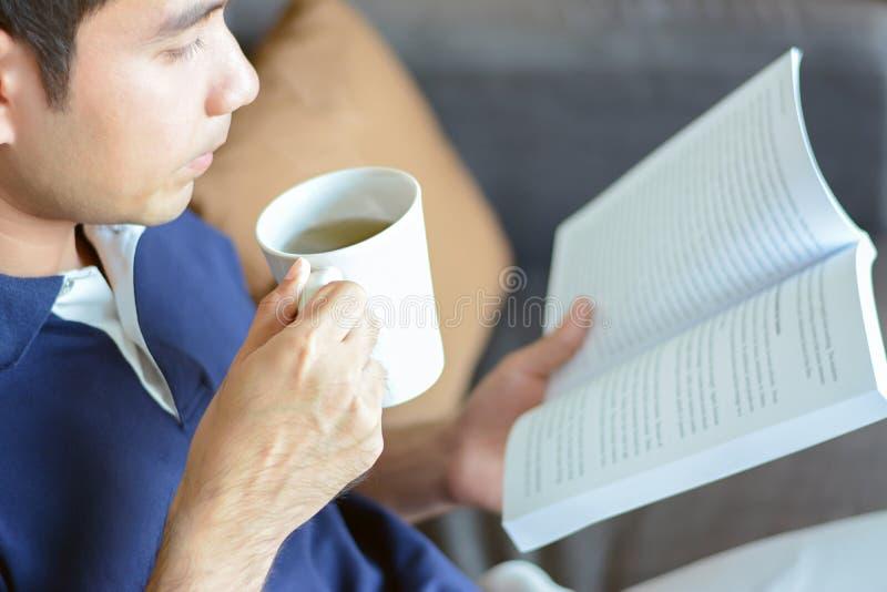 Un libro de lectura del hombre con la taza de té caliente en otra mano imagen de archivo