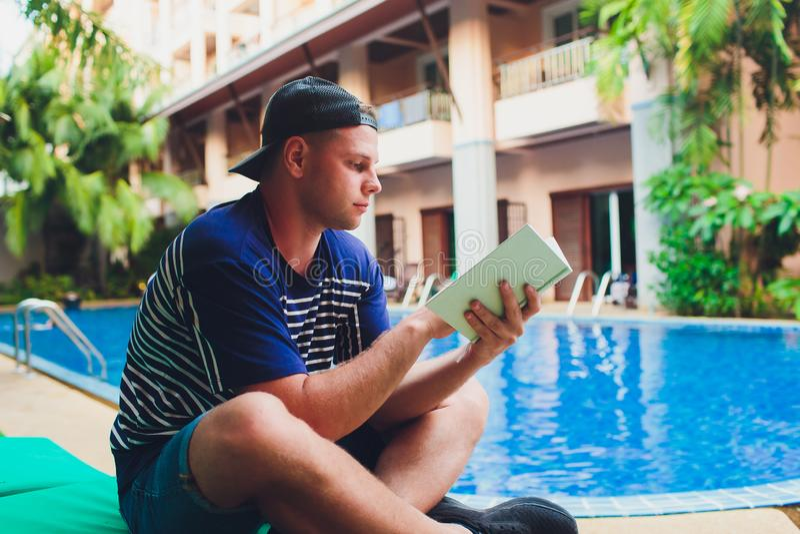 Un libro di lettura dell'uomo accanto alla piscina nel giardino immagini stock