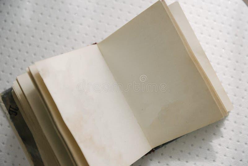 Un libro en blanco abierto está en la tabla Un libro abierto con las páginas en blanco está en la tabla fotografía de archivo libre de regalías
