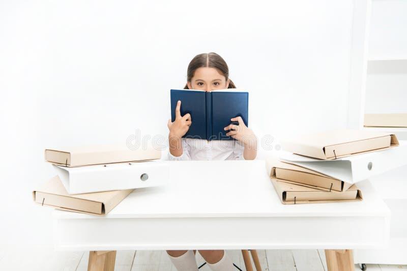 Un libro interesante Libro de la lección de la lectura de la niña en escuela El pequeño alumno tiene lección de la literatura Col imagen de archivo libre de regalías